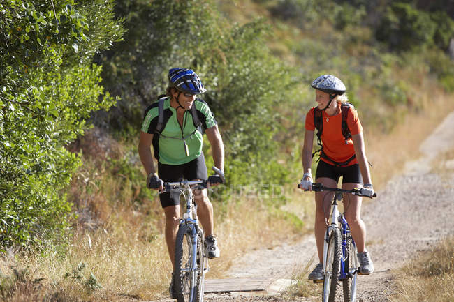 Couple with rucksacks and cycling helmets mountain biking on woodland trail — Stock Photo