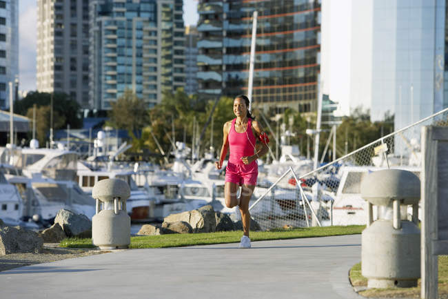 Woman wearing pink sports vest and shorts jogging, listening to MP3 player strapped to arm — Stock Photo
