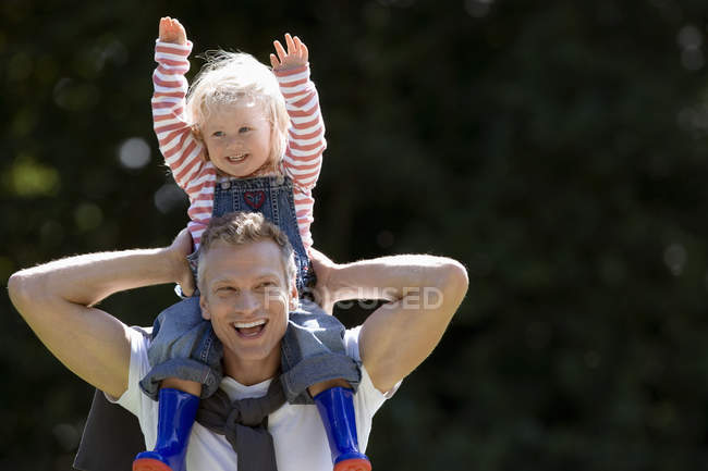 Portrait of happy father carrying daughter on shoulders — Stock Photo
