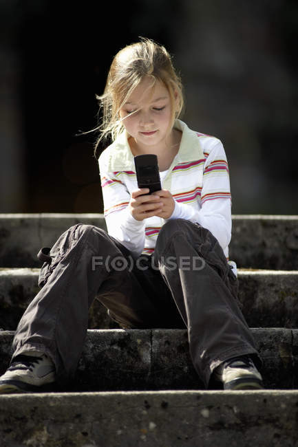 Front view of girl sitting on steps and text messaging on mobile phone — Stock Photo