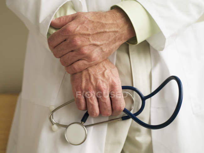 Mature doctor, in laboratory coat, holding stethoscope, close-up, mid-section — Stock Photo