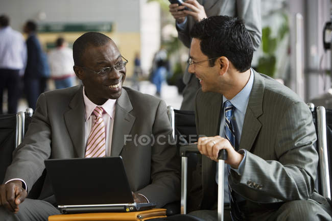 Two businessmen sitting in airport terminal, man using laptop — Stock Photo
