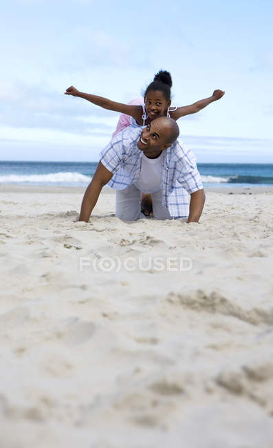 Daughter balancing on father back — Stock Photo