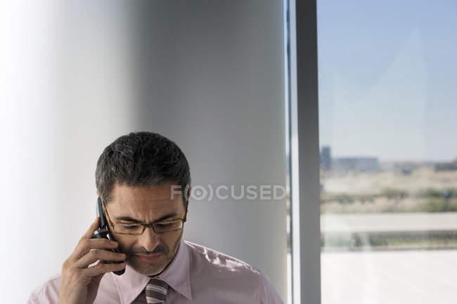 Uomo d'affari maturo portando gli occhiali, utilizzando il telefono cellulare al lato della finestra e guardando verso il basso — Foto stock