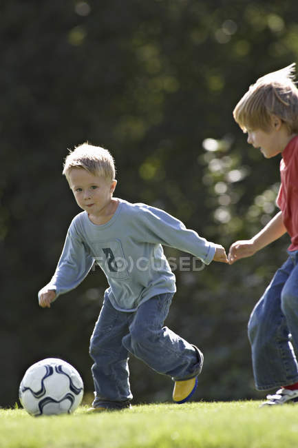 Closeup view of two young boys playing soccer in summer park — Stock Photo