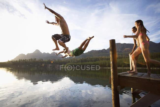 Vue de côté de quatre jeunes adultes, plongée depuis la jetée dans le lac au coucher du soleil — Photo de stock