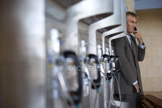 Seitenansicht der Geschäftsmann mit öffentliche Telefonzelle, Fokus auf Hintergrund — Stockfoto