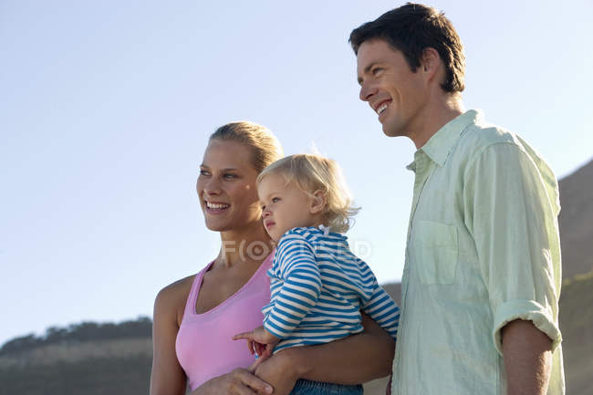 Two generation family standing on beach, mother carrying daughter — Stock Photo