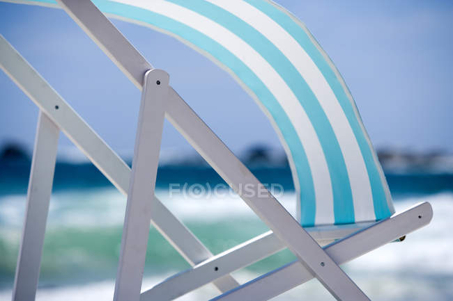 Полосатый бирюзовый лежак, дует ветер — стоковое фото