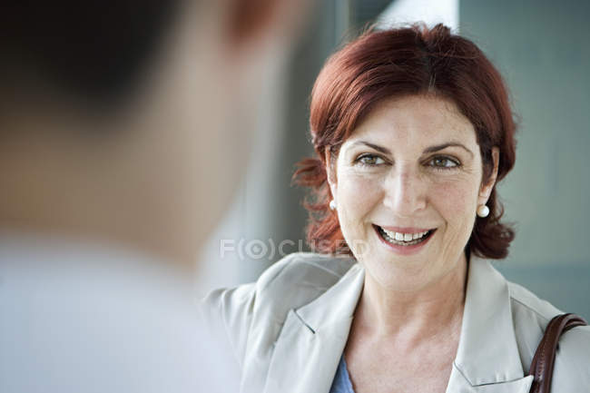 Mature woman looking at camera, focus on background — Stock Photo