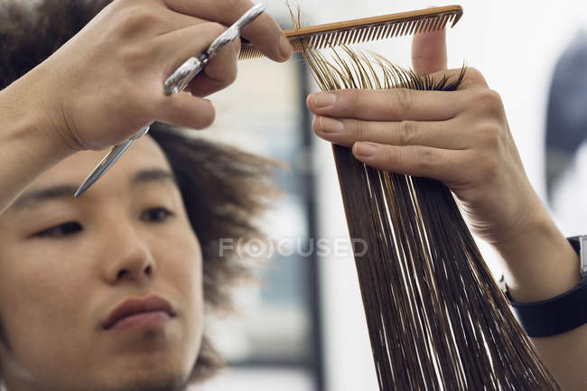Young male hairdresser cutting woman hair in salon on blurred background — Stock Photo