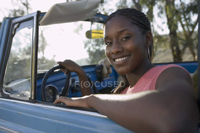 Teenage girl sitting in drivers seat of convertible car — Stock Photo