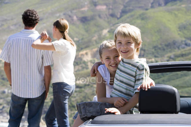 Couple looking at mountain scenery and two children sitting in parked convertible car at roadside — Stock Photo