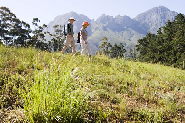Side view of senior couple with rucksacks hiking on mountain trail — Stock Photo