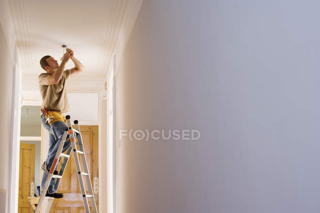 Man standing on step ladder and fixing light fixture in ceiling — Stock Photo