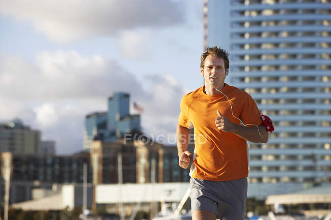 Front view of man jogging and listening to MP3 player strapped to arm — Stock Photo