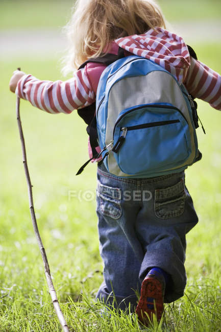 Rear view of girl carrying rucksack and hiking on grass — Stock Photo