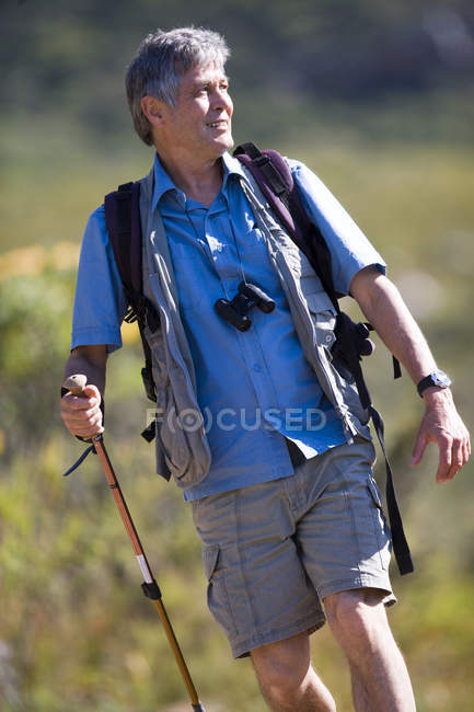 Front view of mature man hiking on mountain trail, carrying rucksack, using hiking pole — Stock Photo