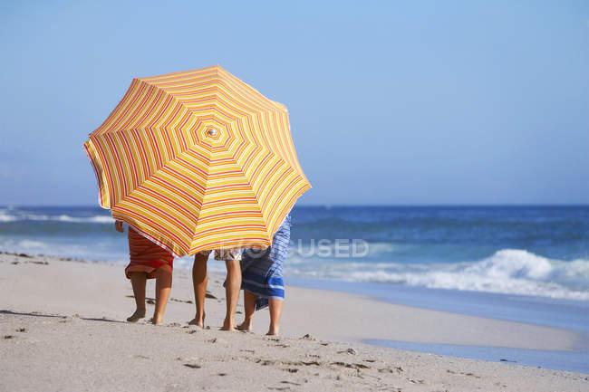 Трое друзей, ходить на пляж, лица скрываются Оранжевый зонтик, вид сзади — стоковое фото