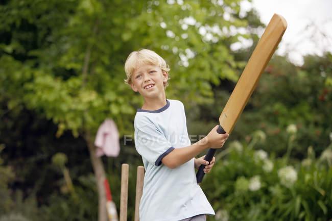 Блондинка хлопчик грає крикету в саду, розмахуючи летюча миша — стокове фото