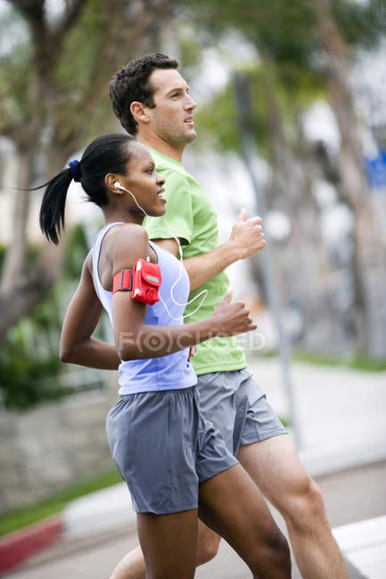 Couple wearing sportswear jogging on pavement and listening to MP3 players strapped to arms — Stock Photo