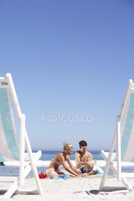 Вид семьи строительства замков из песка на песчаном пляже, шезлонги на переднем плане — стоковое фото
