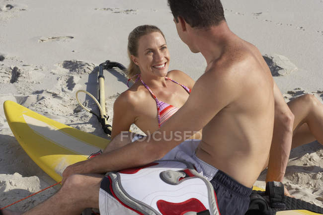 Young smiling couple relaxing beside windsurfer on sandy beach — Stock Photo