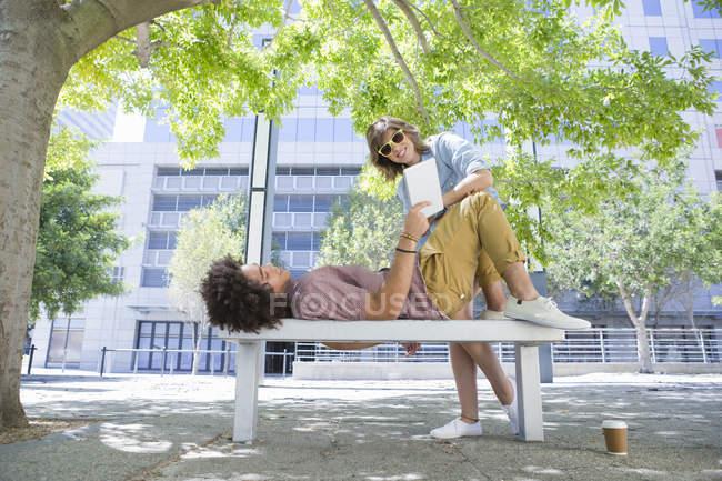 Молодая пара с помощью цифрового планшета на скамейке в городском парке — стоковое фото