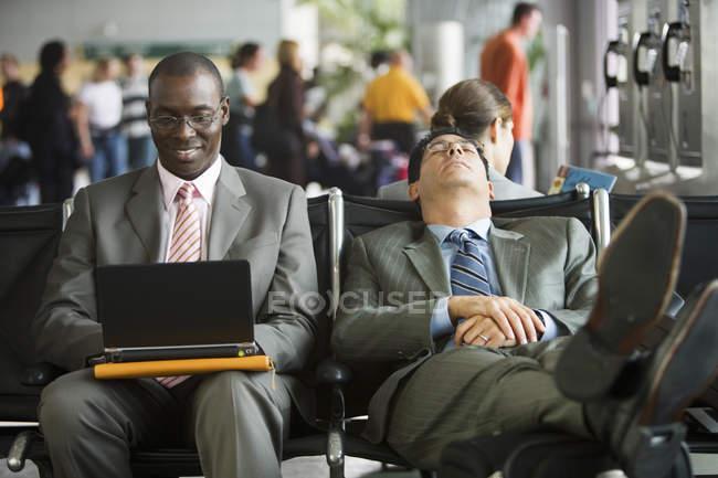 Двоє бізнесменів, сидячи в терміналі аеропорту, одна людина, використовуючи ноутбук, інша людина, відпочиваючи з ніг до ручної поклажі — стокове фото