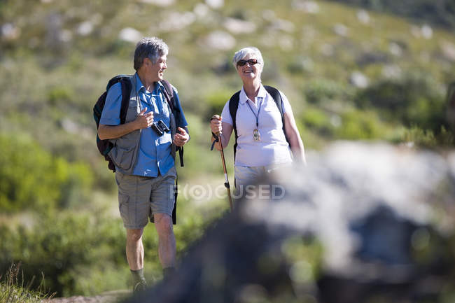 Front view of senior couple with rucksacks hiking on mountain trail — Stock Photo