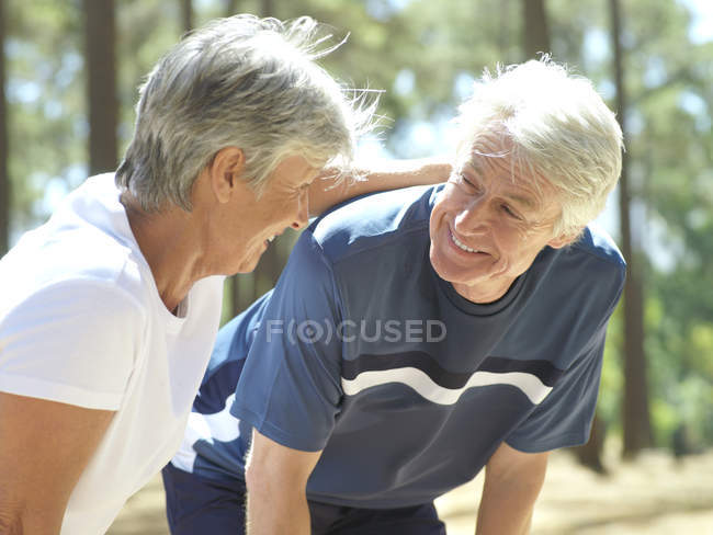 Senior couple in sportswear taking break from jogging — Stock Photo