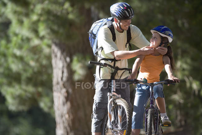 Father and daughter mountain biking on woodland trail, man adjusting strap of girls cycling helmet — Stock Photo