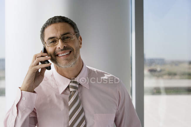 Mature businessman wearing spectacles, using mobile phone beside window — Stock Photo