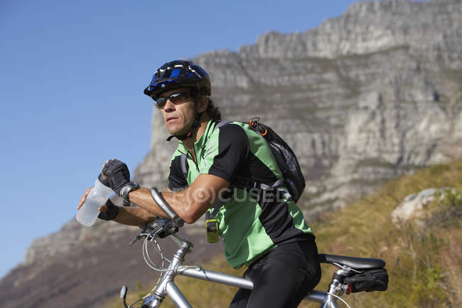 Side view of male mountain biker sitting on bicycle, looking at view, — Stock Photo