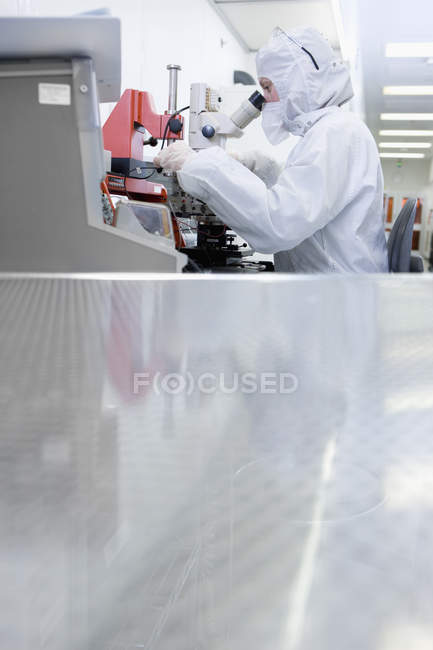 Surface level view of scientist in clean suit examining silicon wafer under microscope — Stock Photo