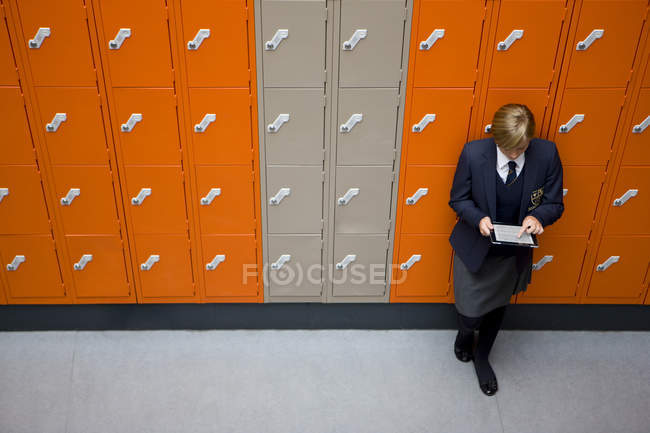 Female student in school uniform leaning on lockers and using digital tablet — Stock Photo