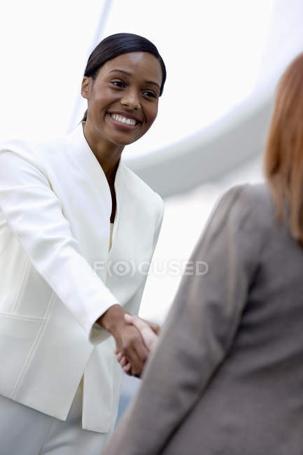 Two businesswomen shaking hands with defocussed background — Stock Photo