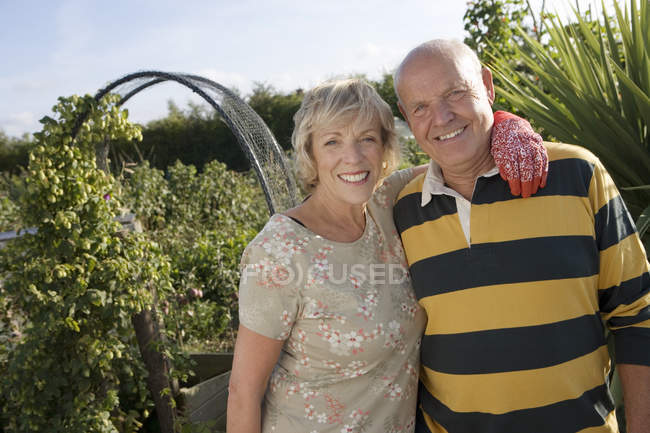 Senior couple standing in garden with arm around each other — Stock Photo