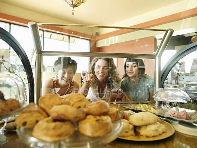Três jovens mulheres olhando para pastelaria em exposição no café — Fotografia de Stock