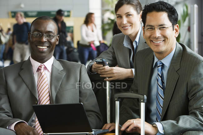 Three business people sitting in airport terminal with laptop and luggage — Stock Photo