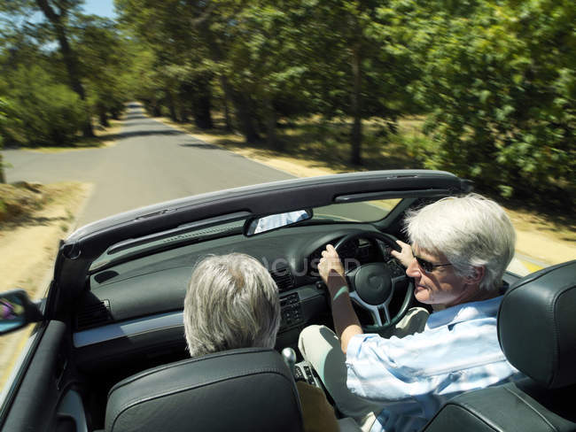 Senior couple driving in convertible car along country road — Stock Photo
