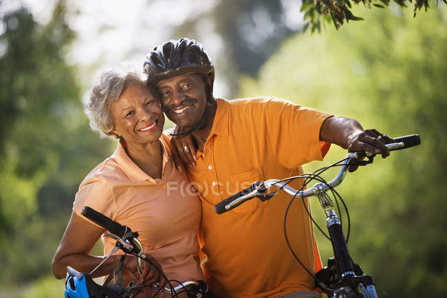Active senior couple standing with bicycles in park and smiling — Stock Photo