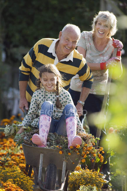 Senior man pushing granddaughter in wheelbarrow in garden with smiling woman on background — Stock Photo