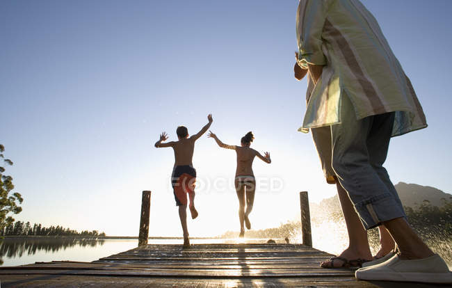 Multigenerational family on jetty at sunset, children jumping into lake — Stock Photo