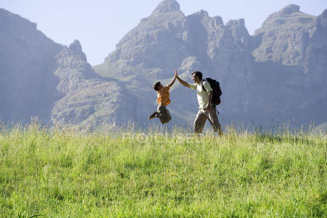 Father and son hiking on mountain trail, boy jumping in air — Stock Photo