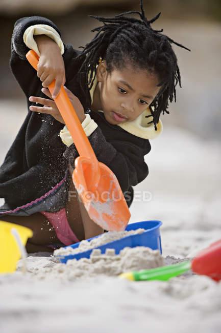 Девушка в игре куртка с ведром и лопатой на пляже, сосредоточиться на фоне — стоковое фото