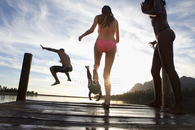 Quatre jeunes adultes portant des maillots de bain, saut depuis la jetée dans le lac au coucher du soleil — Photo de stock