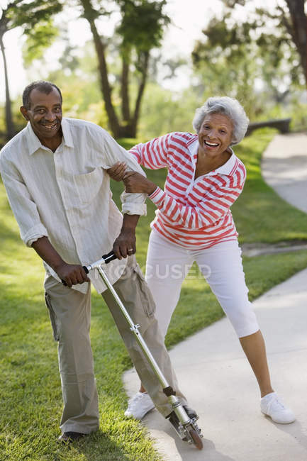 Active senior couple messing about on push scooter in park — Stock Photo