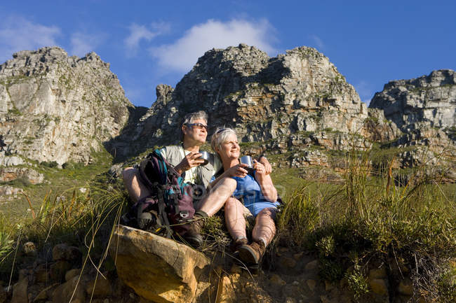Mature couple hiking on mountain trail, taking break and smiling — Stock Photo