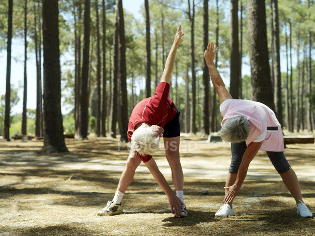 Активних старшим пара в спортивний одяг, що здійснюють під дерево — стокове фото